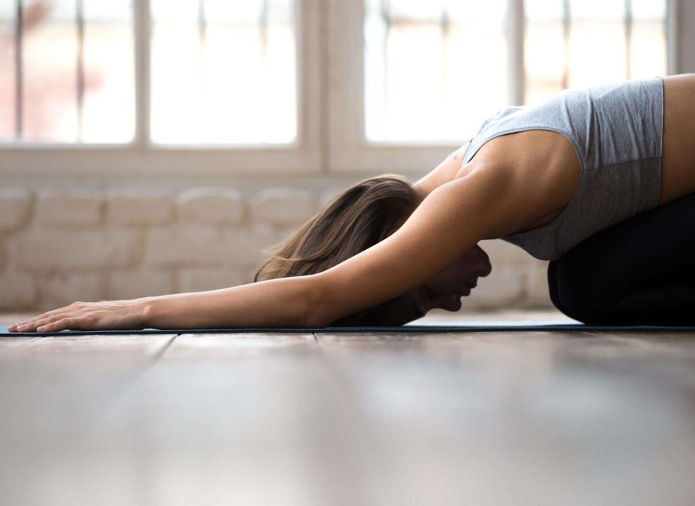 Mulher a fazer exercício de alongamentos de costas