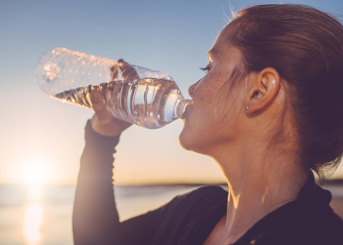 mulher a beber água de garrafa
