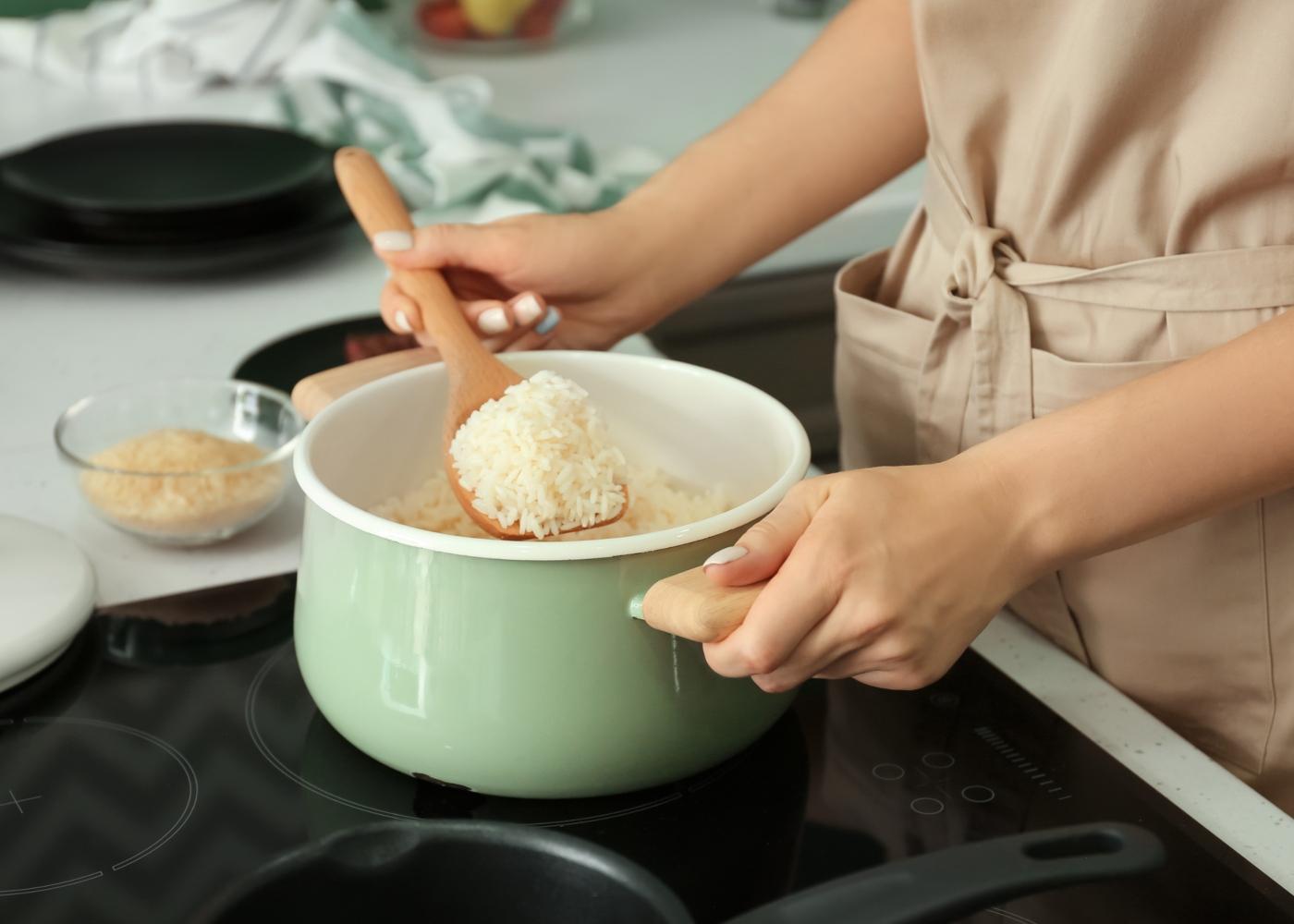 Mullher a cozinhar arroz para o almoço