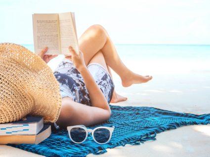 Alergia ao sol: mulher a ler na praia