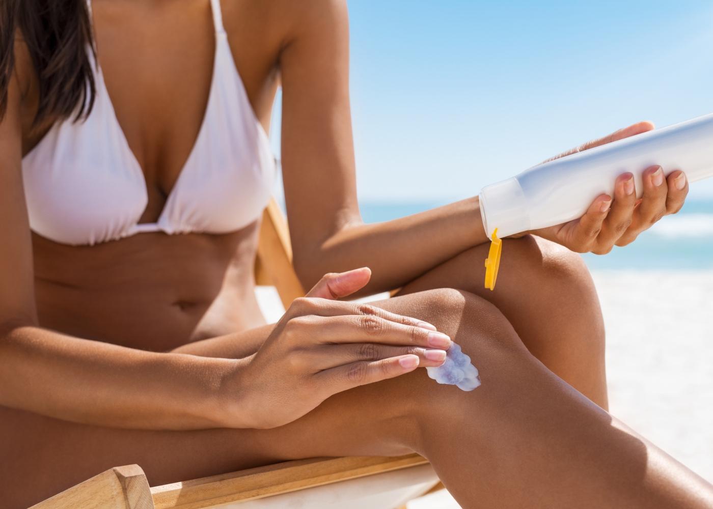 Mulher na praia a aplicar protetor solar nas pernas