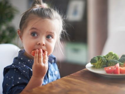 menina a comer legumes