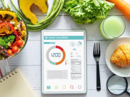 Apps de nutrição e alimentação: tablet em cima de mesa com variedade de alimentos