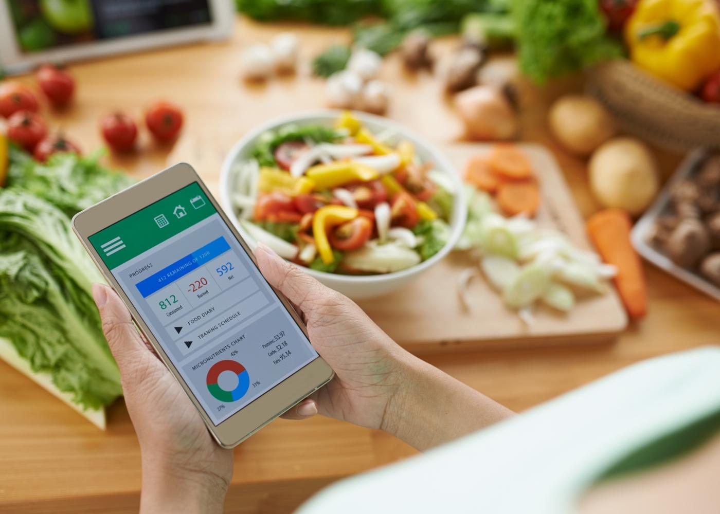 Mulher a consultar apps de nutrição e alimentação enquanto cozinha