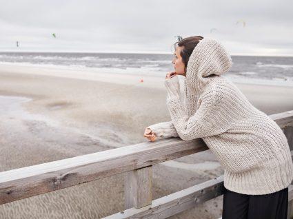 Crise existencial: mulher na praia a olhar para o infinito