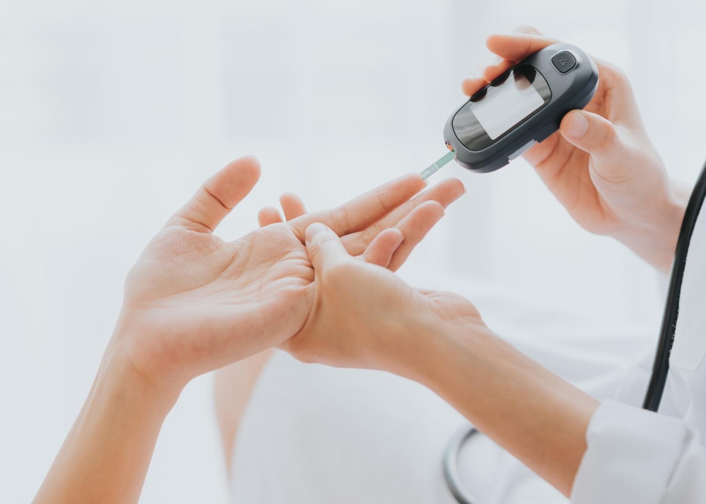 Mulher a fazer picada no dedo para vigiar a glicemia