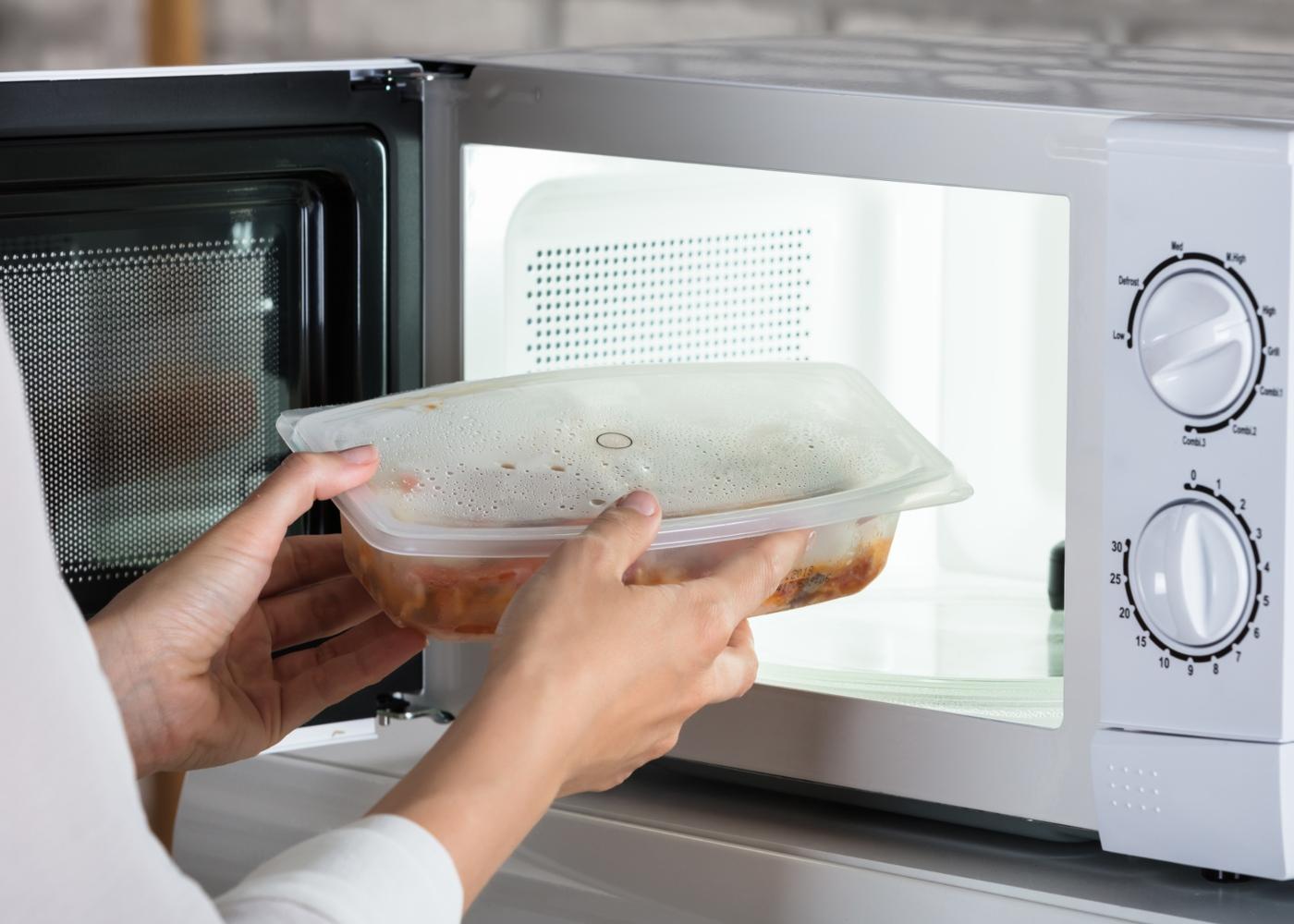 Refeições no micro-ondas: mulher a descongelar comida