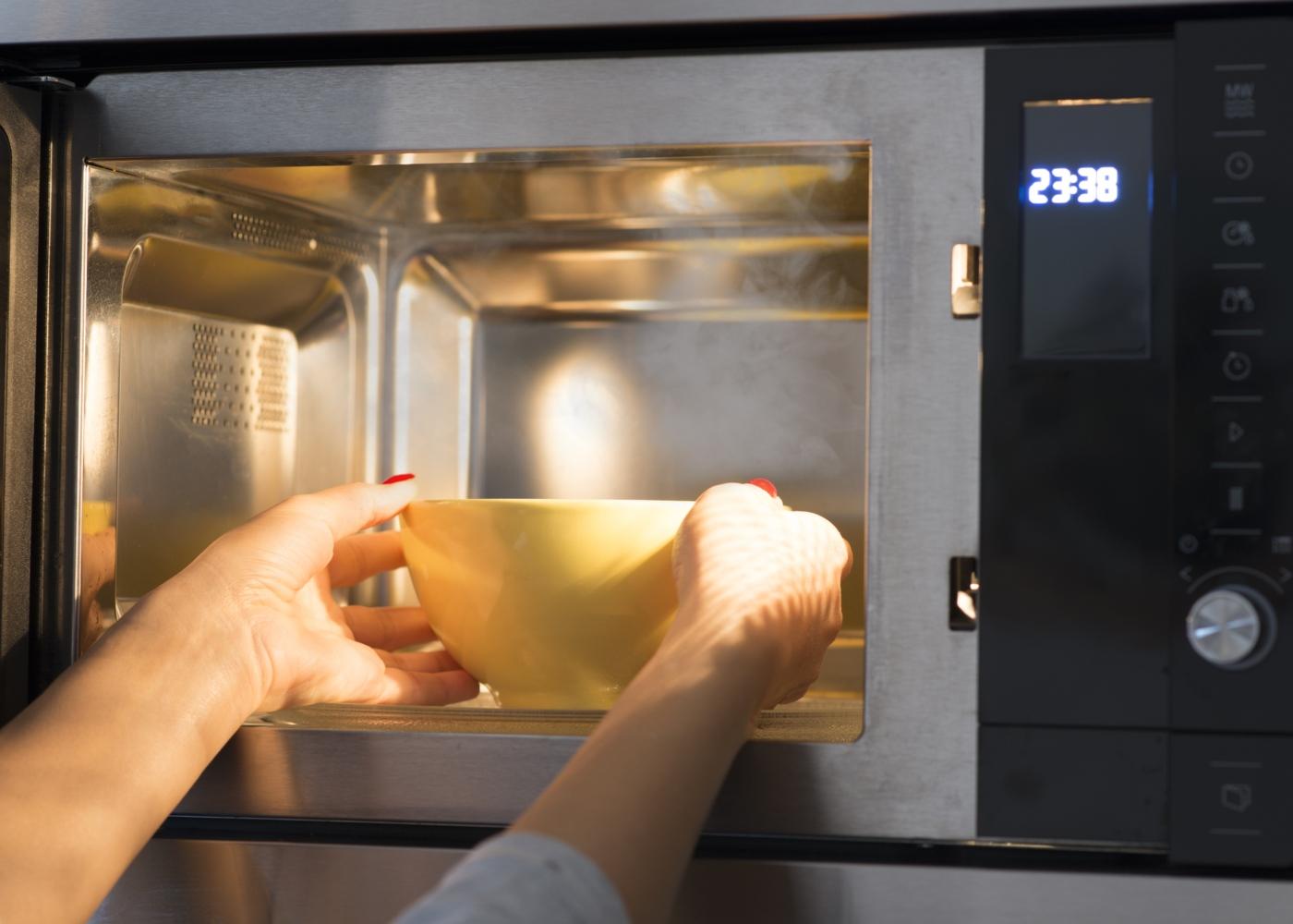 Refeições no micro-ondas: mulher a aquecer sopa