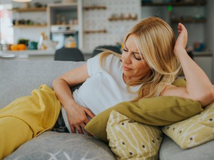 Mulher deitada no sofá com sensação de barriga inchada
