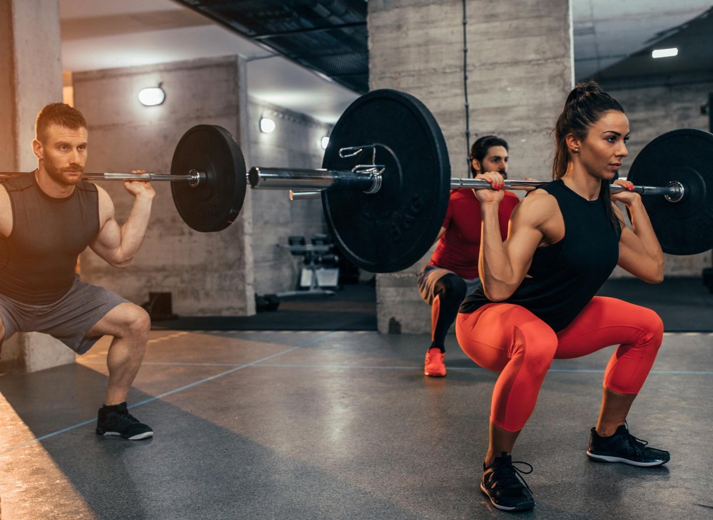 Mulher no ginásio a fazer agachamentos com barra