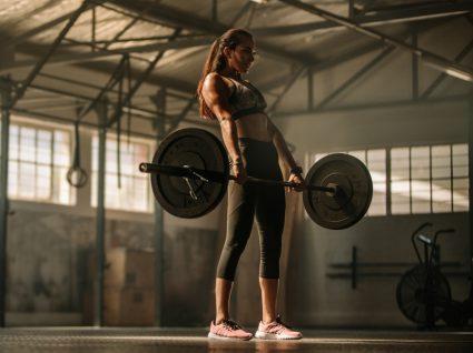 Mulher a levantar barra em treino no ginásio