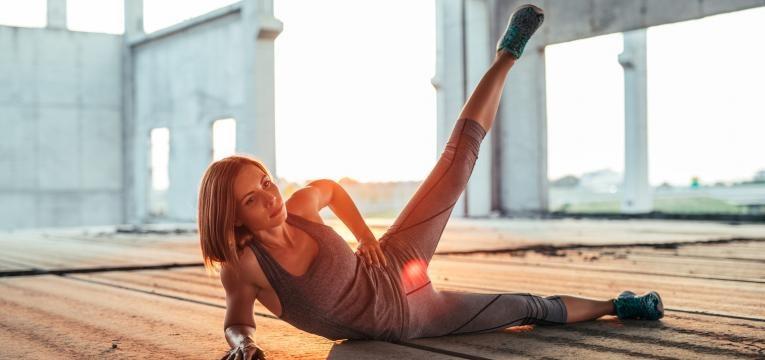 exercícios para tonificar coxas e glúteos: mulher a exercitar abdutor