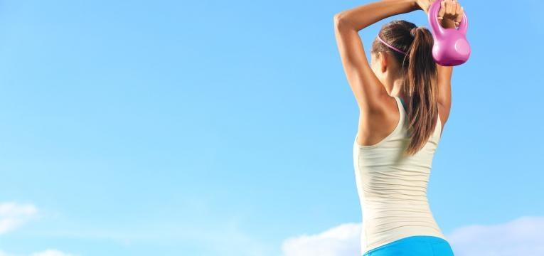 mulher a treinar com peso ao ar livre