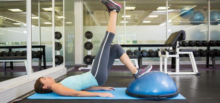 mulher a treinar em ginasio com bola