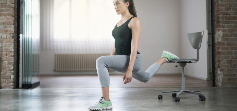 rapariga a fazer lunge com cadeira