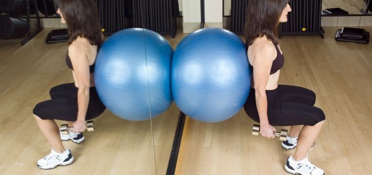 mulher a fazer agachamento com bola