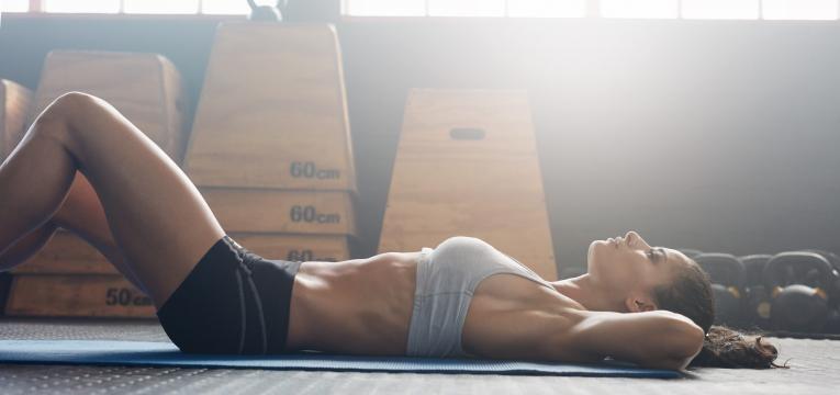mulher deitada a treinar no ginasio