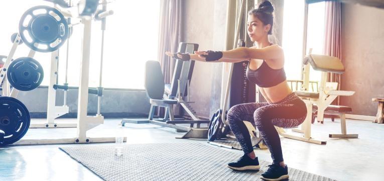 mulher no ginasio a fazer agachamento plano de treino semanal