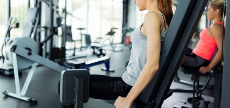 mulher no ginasio a treinar abdutores plano de treino semanal