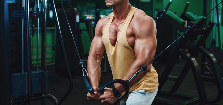 homem a treinar braços no ginasio plano de treino semanal