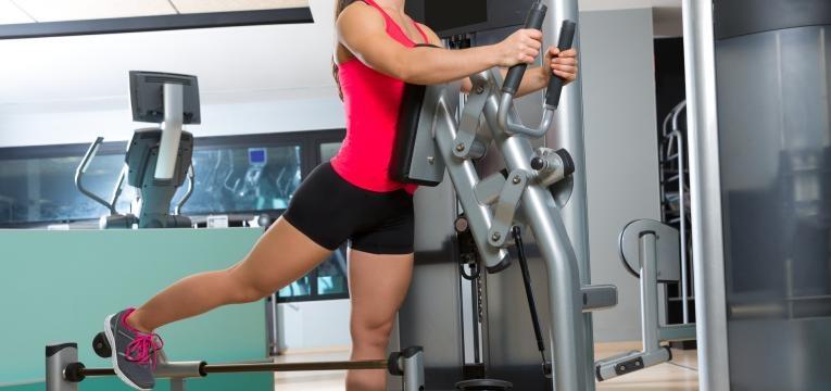 mulher em ginasio na maquina de gluteos plano de treino semanal