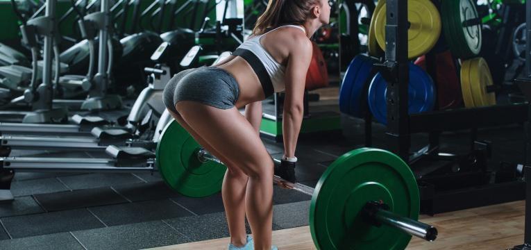 mulher a fazer musculaçao com barra