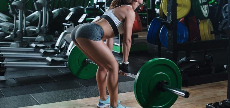 mulher a treinar no ginasio com barra