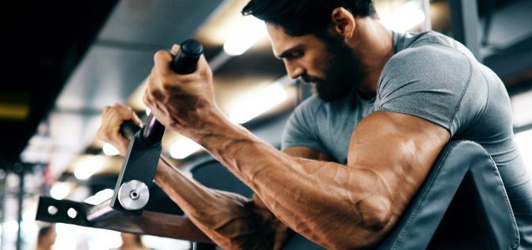 homem a treinar braços na maquina