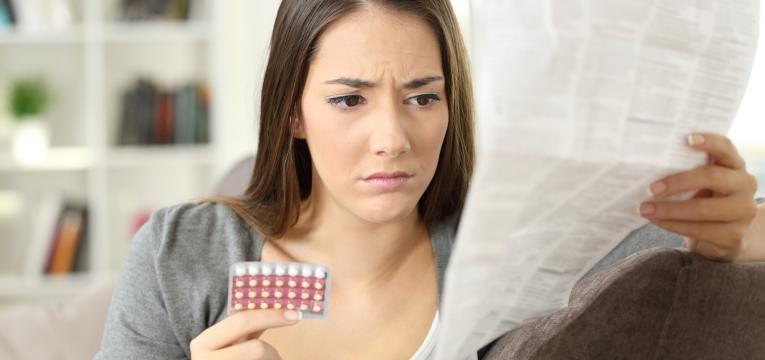 antibiotico corta o efeito da pilula e mulher a ler a bula de medicamento