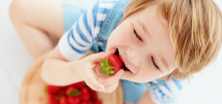 almocos equilibrados para criancas rapaz a comer morangos
