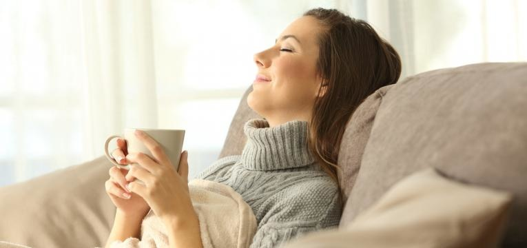 fome antes de jantar mulher a relaxar no sofa com cha