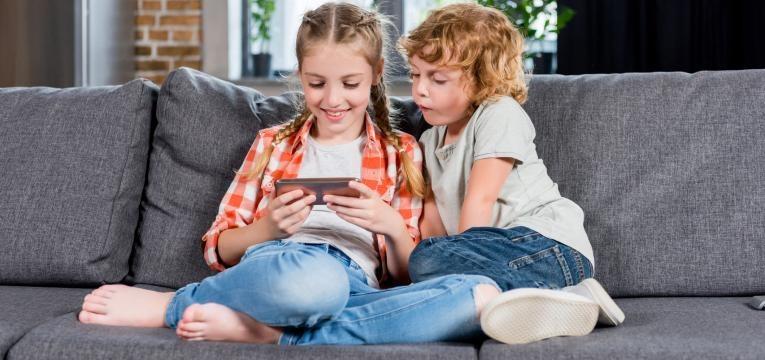 tablets e smartphones para criancas irmaos no sofa a jogar