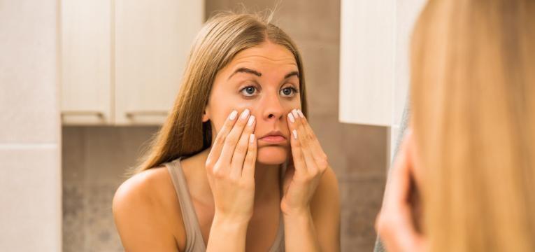 disfarcar olheiras mulher em frente ao espelho com olheiras