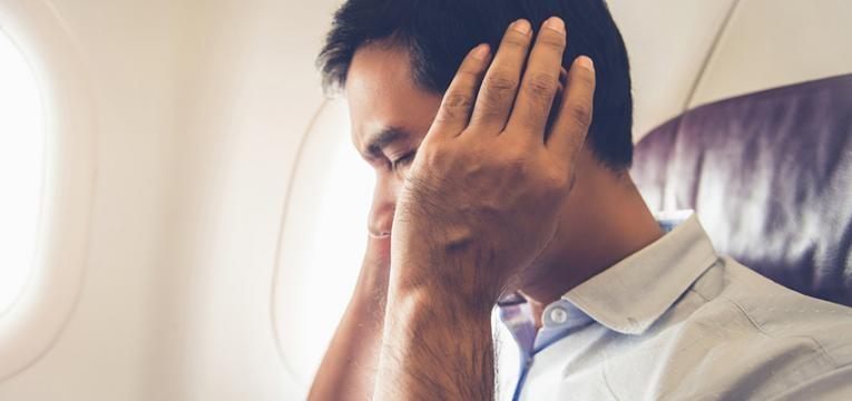 Homem a desentupir o ouvido no avião