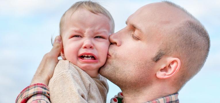crianca a chorar e pai a acalmar