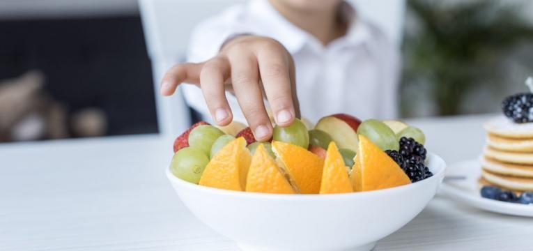 crianca a comer fruta