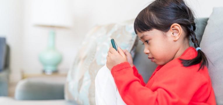 novas tecnologias no desenvolvimento da crianca e menina no telemovel