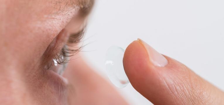 homem a colocar lentes de contato