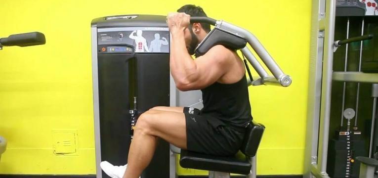 homem a executar abdominal sentado na máquina sem apoio das pernas