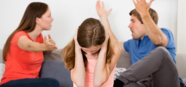 pais a discutir em frente a crianca