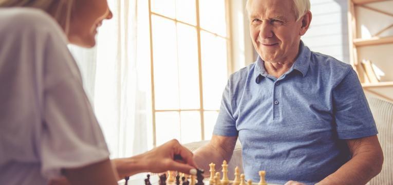 idoso a jogar xadrez com voluntaria