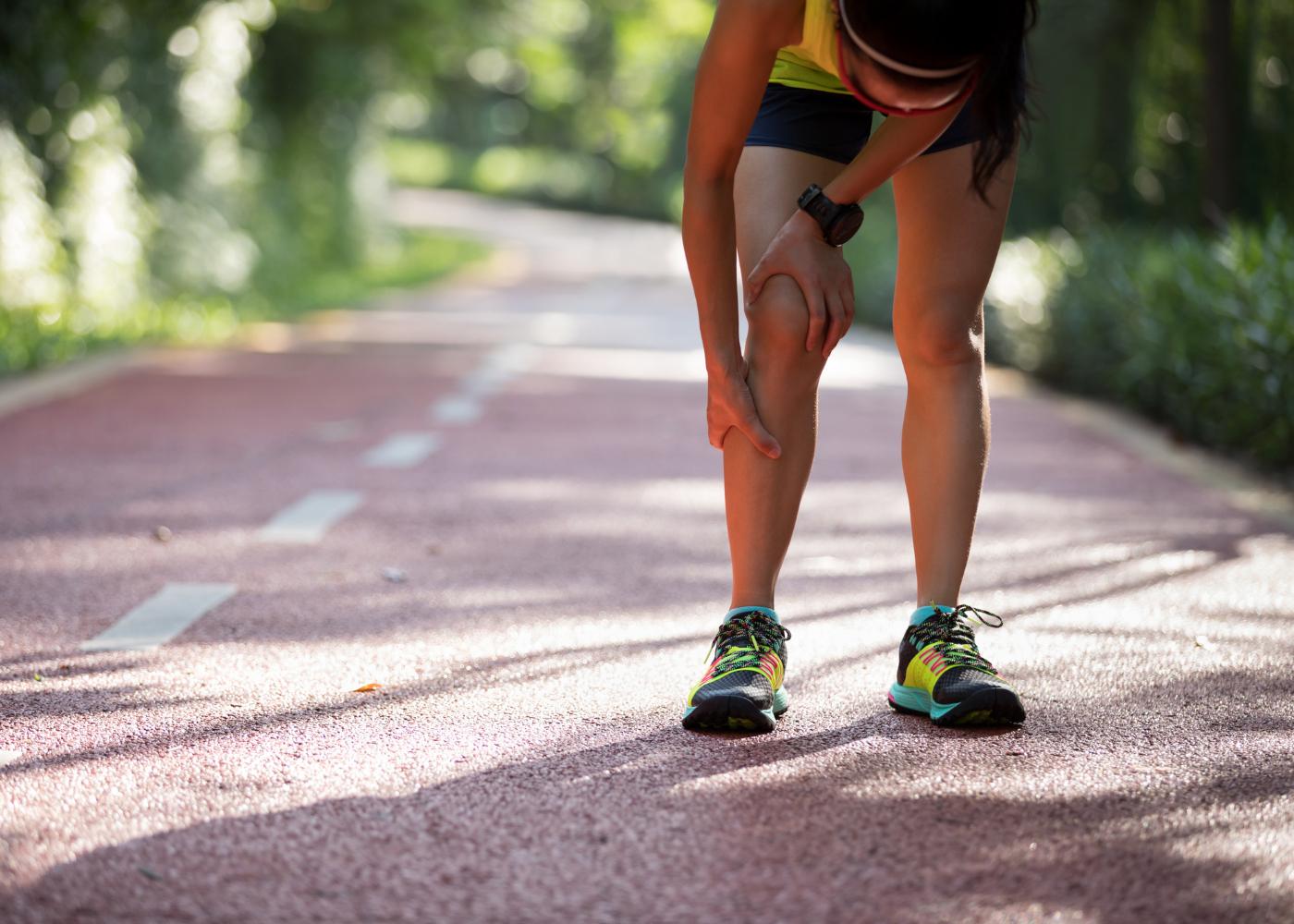 atleta com dor nas pernas a correr
