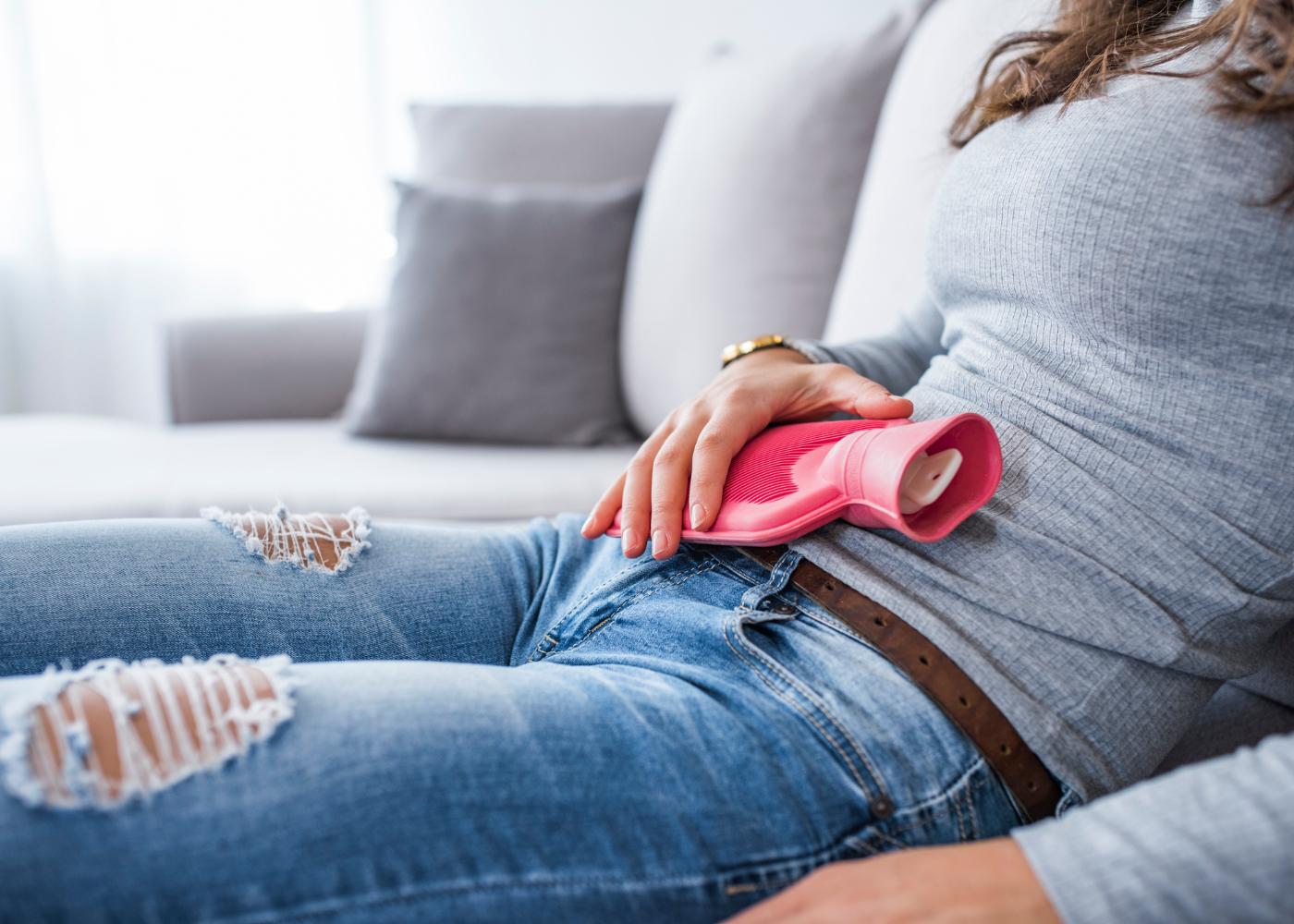 Mulher com botija na barriga por causa das dores menstruais