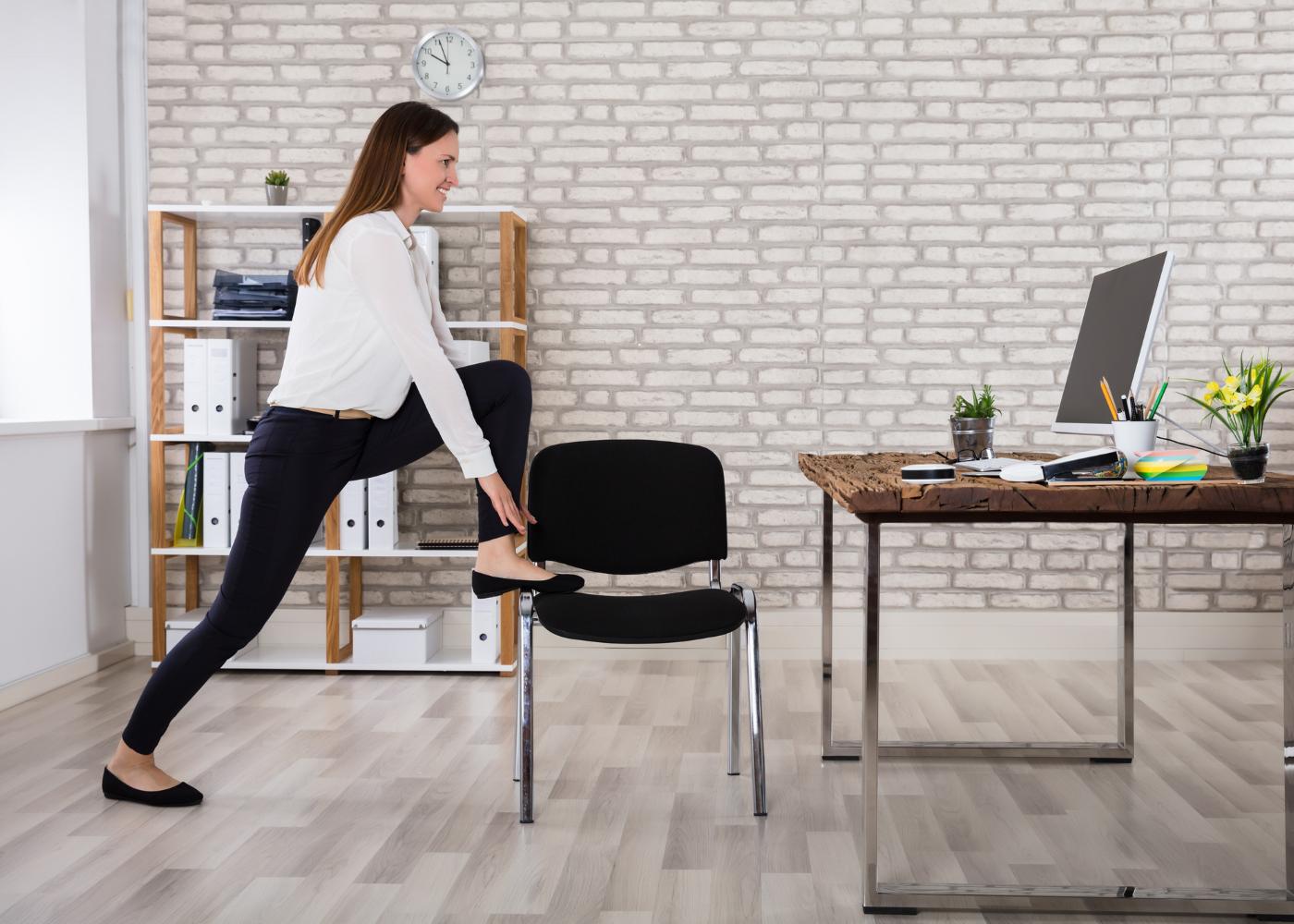 mulher a subir para cadeira no escritório