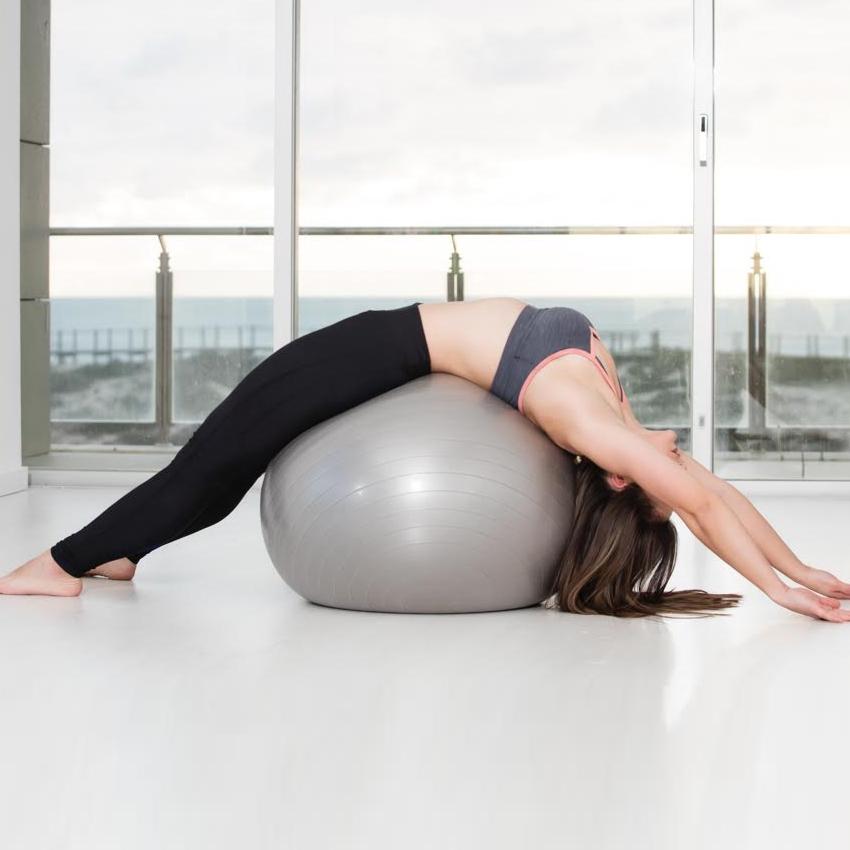 mulher a fazer pilates com bola