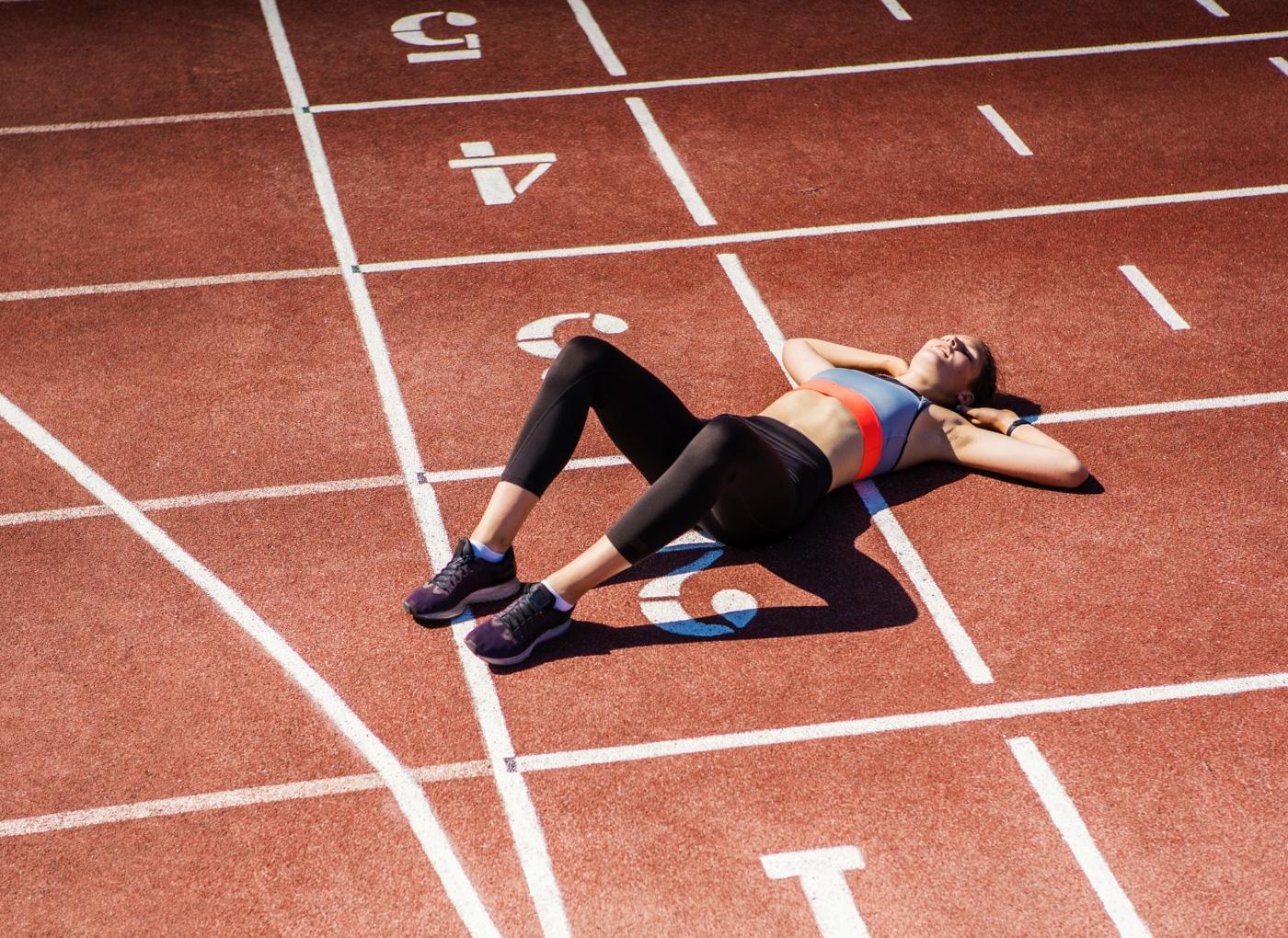 Mulher deitada numa pista de atletismo a descansar