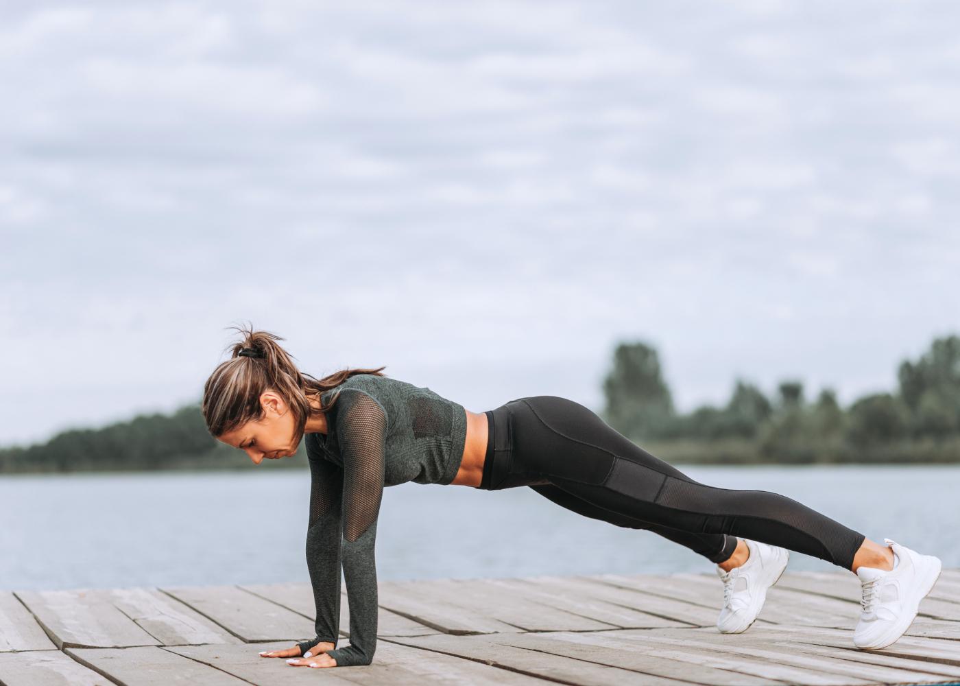 Mulher a fazer exercício de prancha à beira rio