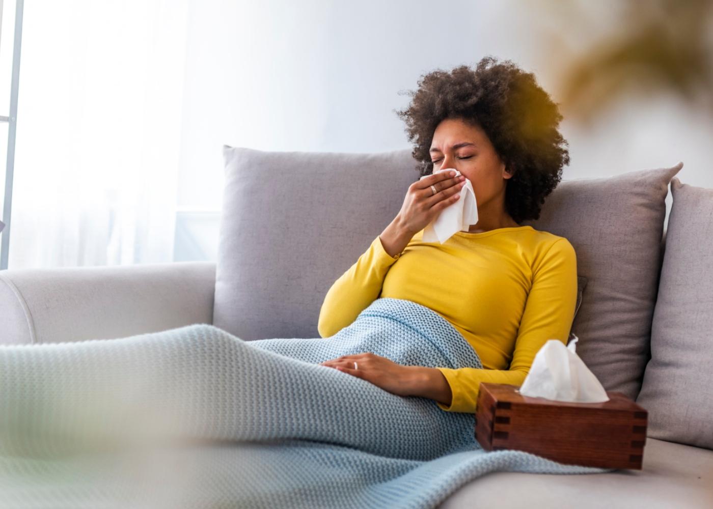 Mulher com constipação deitada no sofá