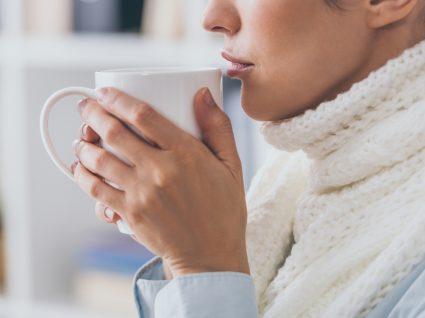 Mulher com gripe a beber chá