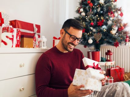homem a abrir presentes de Natal